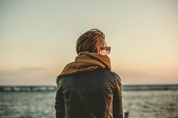 Woman wearing leather jacket sitting by ocean