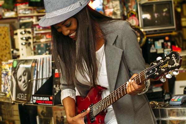 Woman tests guitar and guitar maintenance
