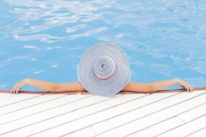 Woman sitting near swimming pool with dry skin