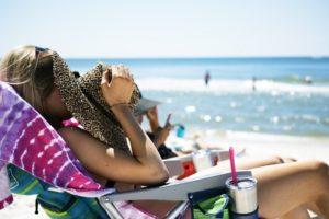 woman sun bathing near oceanside on beach in the summer