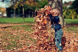 Child playing outdoors in pile of leaves with fall allergies