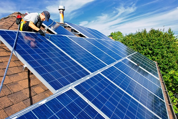 Man installing clean energy photovoltaic solar panels on roof