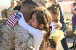 Military man embraces daughter after returning home from deployment