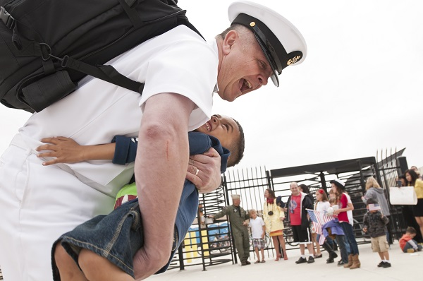 Military father hugs son after reuniting.