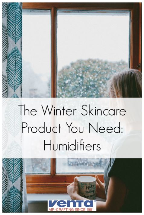 Woman standing in front of window applying new winter skincare routine