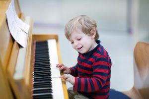 Little boy playing wooden instrument piano