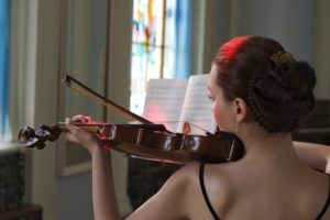 Woman playing wooden instrument violin in church