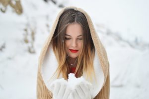 Woman in snow updating winter skincare