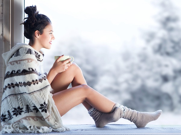 Woman sips tea in dry air during cold winter.