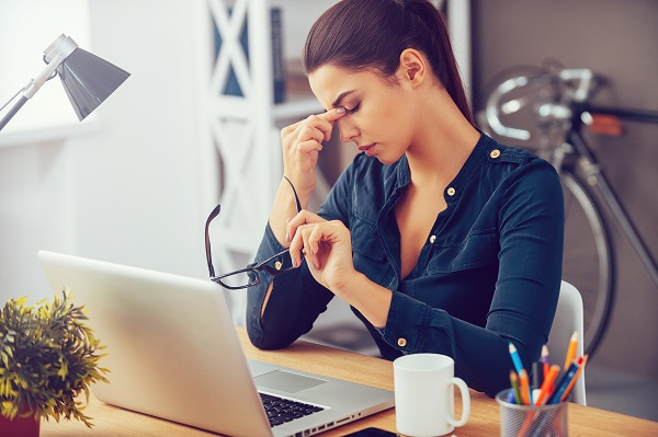 Woman has headache at desk in office due to dry air