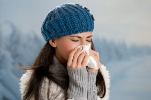 Sick woman blowing her nose during flu season