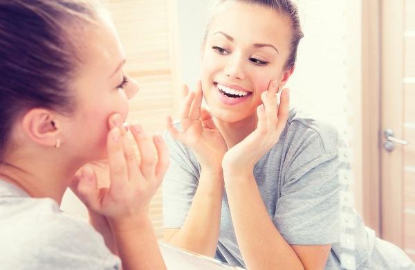 Woman inspects skin in mirror