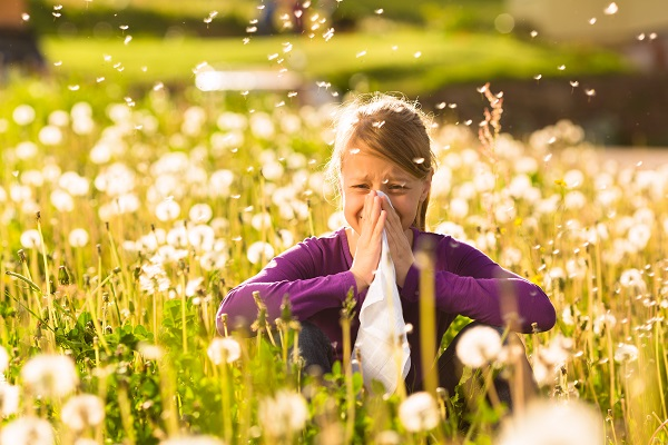 May is asthma and allergies awareness month as woman sneezes in field