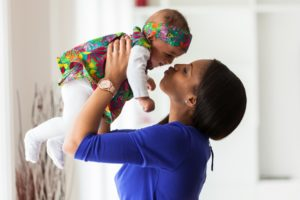 Woman holds baby inside while breathing healthy indoor air quality